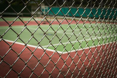 Tennis court in metal fence Royalty Free Stock Photography