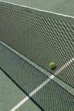 Tennis court net and ball. Tennis ball behind a net Stock Images