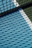 Tennis court net casts shadow on blue ground stock photo