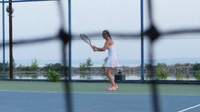 On the tennis court - personal trainer training a tennis player. Net in front stock video footage