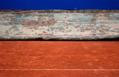 Tennis court protective cover. A clay tennis court gets uncovered after a rain storm. The cover protects the clay surface during a storm Stock Image