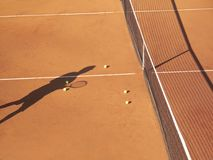 Tennis Court. Shadow of tennis player at net with scatttered tennis balls on clay court royalty free stock image