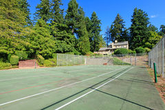 Tennis court wuth Large brown house exterior with summer garden. Stock Images
