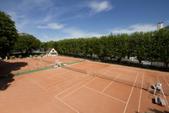 Tennis courts. View of three clay tennis courts, with the clubhouse visible in the far corner Stock Photos