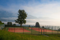 Tennis courts in the morning mist Stock Photos