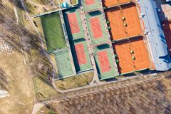 Tennis courts between trees of public park. aerial top view in sunny day royalty free stock images