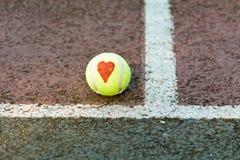 Tennis d'amour - aimez le coeur dessiné sur la balle de tennis Images stock
