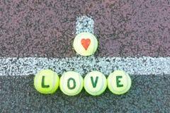 Tennis d'amour - le mot et le coeur forment tiré sur des boules Image stock