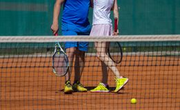 Tennis day . Man and woman love on tennis court. Male and female tennis players in action on the court on a sunny day Royalty Free Stock Photography