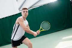 Tennis de jeu de jeune homme extérieur sur la cour orange photos stock