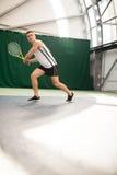 Tennis de jeu de jeune homme extérieur sur la cour orange photo libre de droits