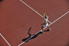 Tennis del gioco della giovane donna esterno Immagine Stock