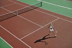 Tennis del gioco della giovane donna esterno Fotografie Stock