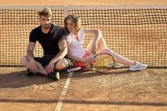 Tennis dell'uomo e della donna con la racchetta Le coppie nell'amore si siedono alla rete del tennis sul campo in argilla fotografia stock libera da diritti