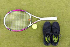 Tennis equipment set of tennis racket, ball and male sneakers on Royalty Free Stock Image