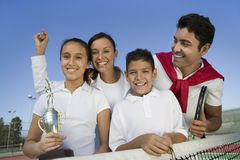 Tennis Family at net on tennis court daughter holding trophy portrait Royalty Free Stock Photography