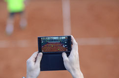 Tennis fan taking photo with smart phone Royalty Free Stock Photos
