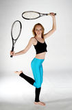 Tennis Fun. A young model dancing with two tennis rackets royalty free stock photos