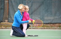 Tennis Fun. Mother teaching daughter how to play tennis royalty free stock photo
