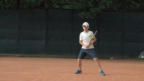 Tennis game, ambitious tennis player adolescent boy concentrating and focusing on game and racket hit ball on red court. In open air stock video