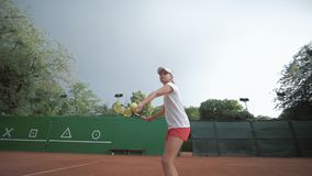 Tennis game, ambitious sport player adolescent girl hitting racket on ball at professional red court during tournament. On open air, Slow motion stock footage