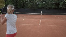 Tennis game, sports player adolescent girl with contestant hitting racket on ball pass through net to each other at. Court during championship stock footage