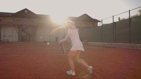 Tennis game on sunny day at tennis court young sportive woman playing professional tennis. Professional tennis player stock video footage