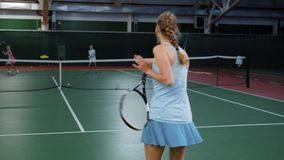 Tennis game. Young girl playing against two young players. Practicing in tennis. Back view. Indoor court stock video