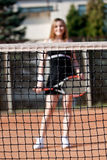 Tennis girl. Net in focus with blured girl standing on a tennis court for lessons with raquet Stock Images