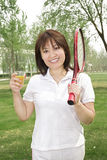 A tennis girl. Is pleased drinking on grass Royalty Free Stock Image