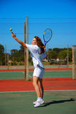 Tennis girl. Full body of a beautiful caucasian white teenage girl with concentrating facial expression, focusing on hitting the ball, during summer training on royalty free stock photography