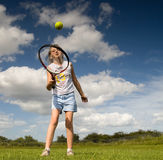 Tennis girl. Girl playing with tennis racket and ball in the park Royalty Free Stock Photography