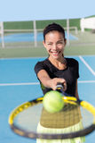 Tennis girl showing racquet and ball on court. Tennis girl holding racquet / tennis racket and ball on court. Asian woman sport athlete showing sports equipment Royalty Free Stock Photos