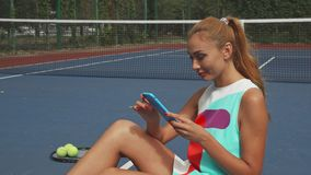 Tennis girl surfing the net while relaxing stock video