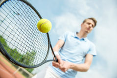 Tennis. Handsome tennis player on hard court serving the ball stock image