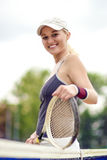 Tennis and Health Life Concept: Portrait of Positive Smiling Pro. Fessional Female Tennis Player Posing with Racquet.Vertical Image Orientation Royalty Free Stock Photo