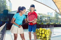 Tennis instructor teaching the correct grip for holding the racket. Chinese tennis instructor smiling while teaching a beginner female player the correct grip royalty free stock photo