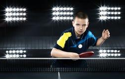 Tennis-joueur de petit garçon dans le jeu sur le noir Images stock