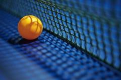 Tennis knackar pongbollen med netto Arkivfoton