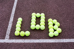 Tennis Lob Shot. Created using tennis balls on a hard court surface Royalty Free Stock Photos