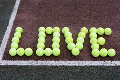 Love Tennis. Created using tennis balls on a hard court surface Royalty Free Stock Photography