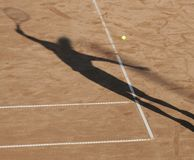 Tennis man shadow. Tennis man in action on royal court, shadow royalty free stock images