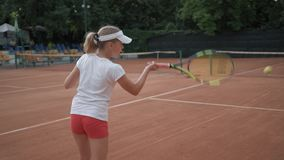 Tennis match, sports player child girl with contestant hitting racket on ball pass through net to each other at court. During tournament stock footage