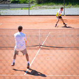 Tennis match of two male players. Male tennis match competition on sand court stock photography