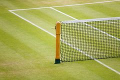 Tennis net. Detail of a tennis net and post on a grass court Royalty Free Stock Photo