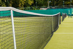 Tennis net on the background of grass courts Royalty Free Stock Photo