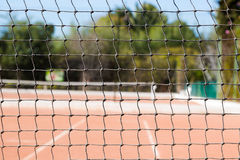 Tennis net edge close up on orange sand tennis court Stock Photo