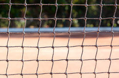 Tennis net edge close up on orange sand tennis court Royalty Free Stock Photography