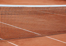 Tennis net at empty red gravel court Stock Image