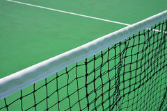 Tennis net in green court Stock Photo